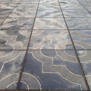 View enlargement of Squares and circles form ornate patterns on the footpath, in Chita.