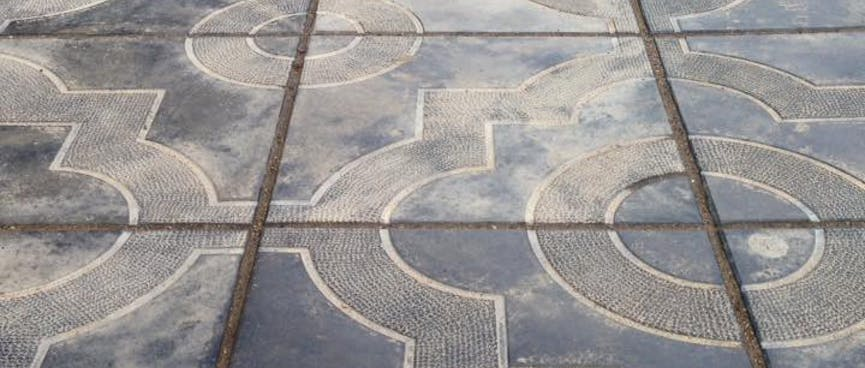 Squares and circles form ornate patterns on the footpath, in Chita.