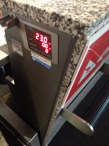 The LED readout at the check-in counter reads 23.0kg.