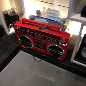 View enlargement of A large red ghetto blaster.