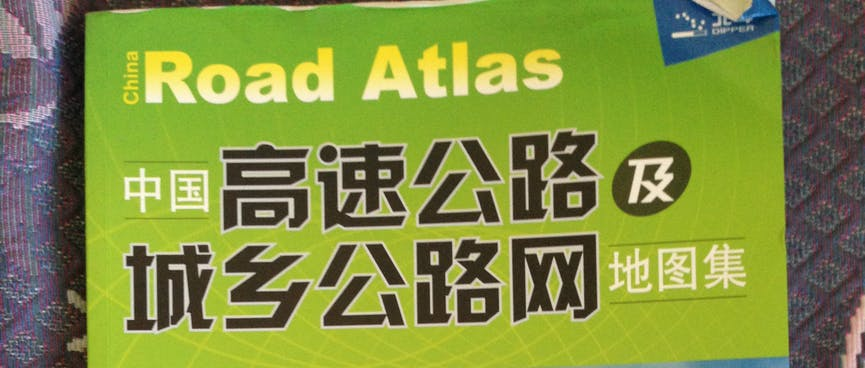 The soft cover of an atlas shows Chinese writing and pictures of empty highway.