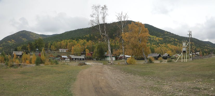 Wooden houses surrounded by forest, and in the background, a large hill.