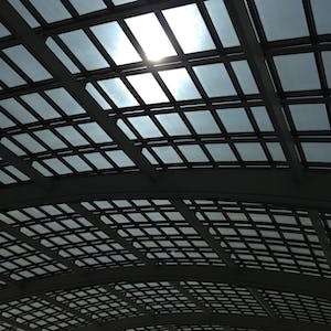 View enlargement of A large curved glass ceiling is supported by metal framing.