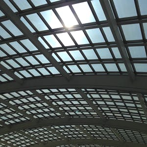 A large curved glass ceiling is supported by metal framing.