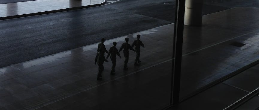 Five soldiers march in single file.
