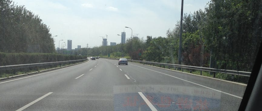 Driving down the three lane expressway towards Beijing city.