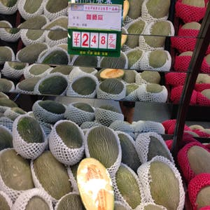 View enlargement of Stacked rock melons are wrapped in plastic mesh.
