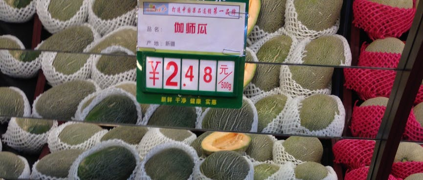 Stacked rock melons are wrapped in plastic mesh.
