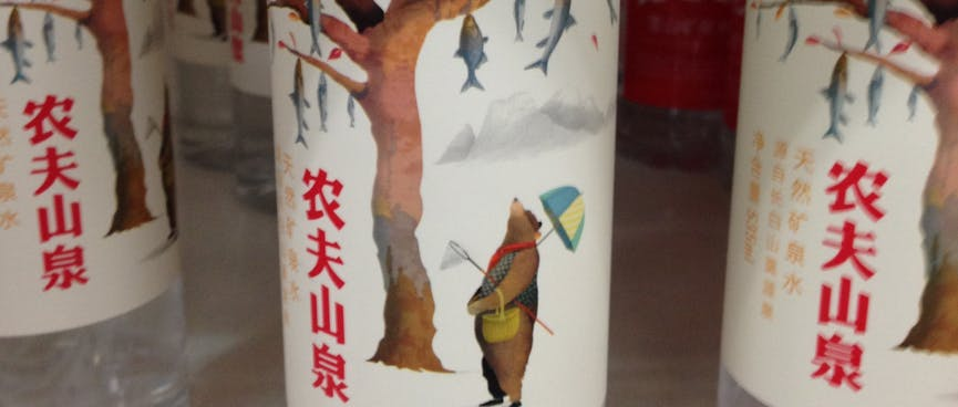 A bear with a fishing net gazes up at a tree of fish, on a water bottle label.