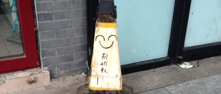 Pen marks on a road cone resemble a happy face.