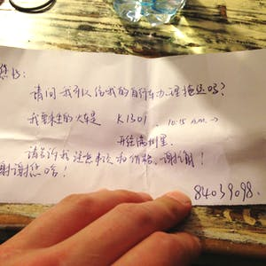 A handwritten note with questions for the Chinese ticket office.