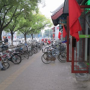 View enlargement of Bicycles are angle parked enmasse on the footpath.