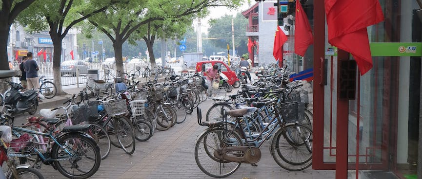 Bicycles are angle parked enmasse on the footpath.