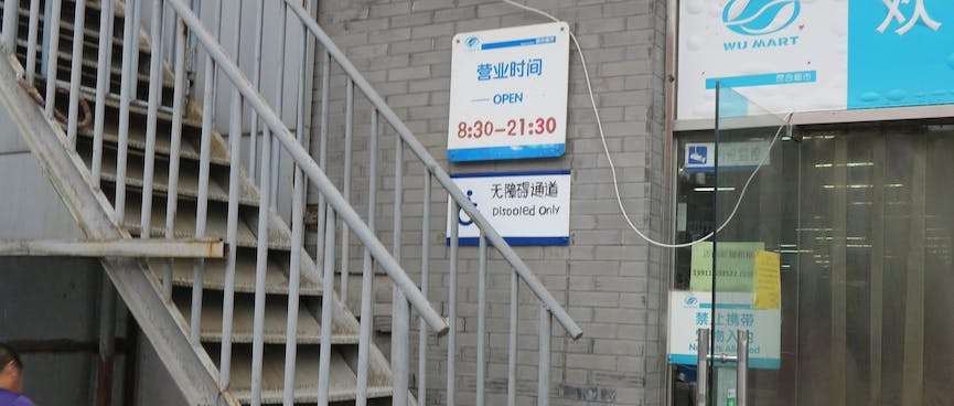 A wheelchair sign outside the Wu Mart reads 'Disooled only'.