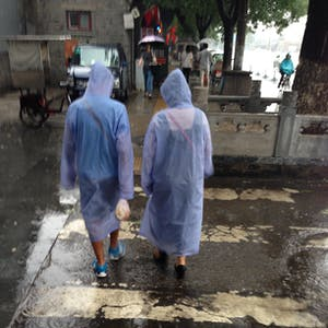 View enlargement of Two people wear see through raincoats to beat the downpour.