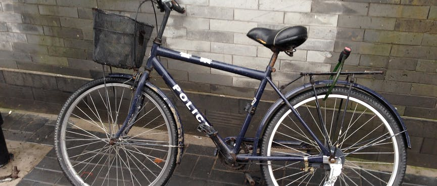 A simple black bicycle reads 'Police'.