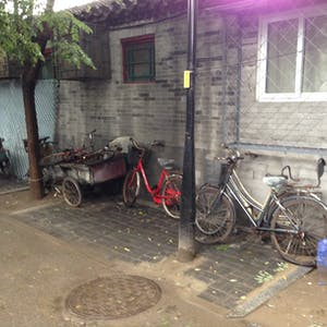View enlargement of Ladies bicycles and a cart with bicycle wheels.