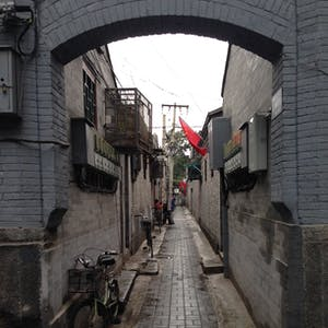 View enlargement of Bikes with baskets line an alleyway.