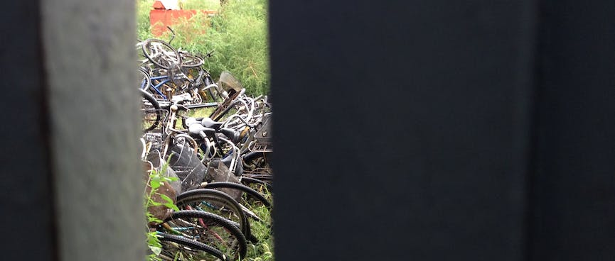 A slit in a gate reveals a pile of old bicycles.