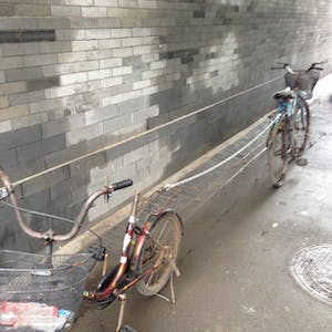 View enlargement of Two bikes are locked together with a long chain.