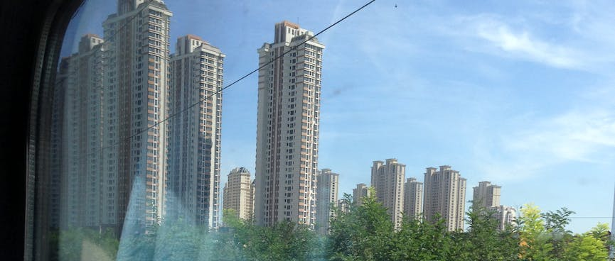 10 high rises buildings next to a grove of trees.