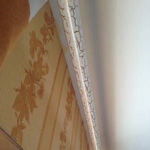 View enlargement of A curtain rail is painted with designer cracks.