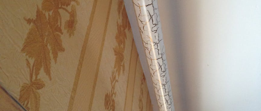 A curtain rail is painted with designer cracks.