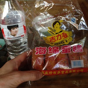 View enlargement of A bottle of water and a packet of sweet breads.