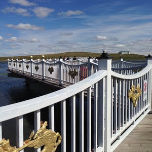 View enlargement of Fence pickets and posts dominate the view over the bridge.