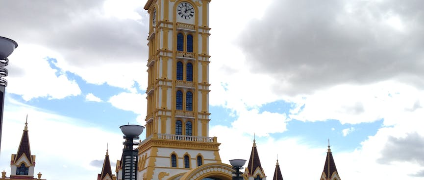 I spread my arms in front of an ornate clock tower.