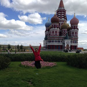 View enlargement of Mandy launches herself into the air, in front of a church with onion shaped domes.