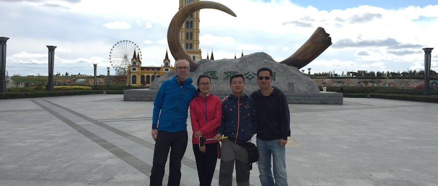 Our group of four poses in front of a mammoth tusk set in concrete.
