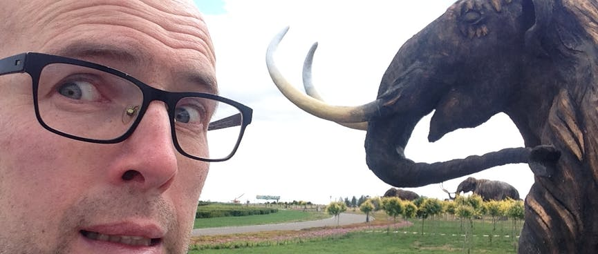 A mammoth's sharp tusks are only inches away from my pale face.