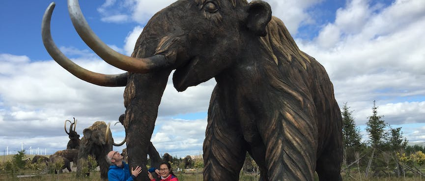 Mandy and I hold on to a mammoth's long trunk.