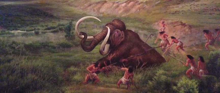 A painting shows locals spearing and lassoing an injured mammoth.