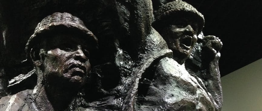 Metal statues depict bare chested miners wearing helmets.