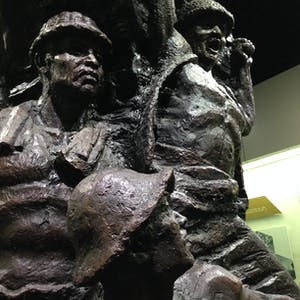 View enlargement of Metal statues depict bare chested miners wearing helmets.