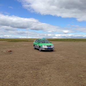 View enlargement of A green taxi stands alone on the steppes.