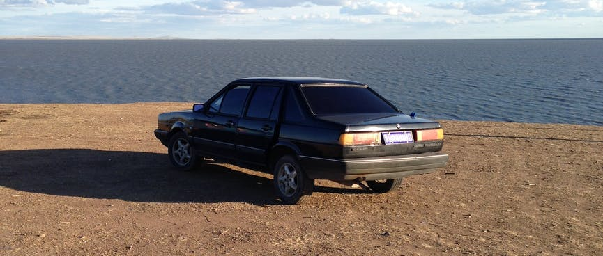 A black car parked on a barren, elevated section of the shore.