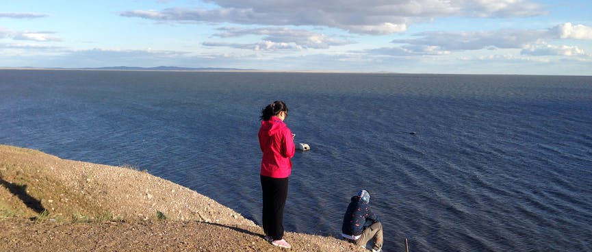 Mandy stands on a high point of the lakeshore with one of the guys.