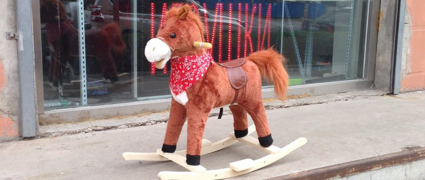 A brown rocking horse wears a red cowboy scarf.