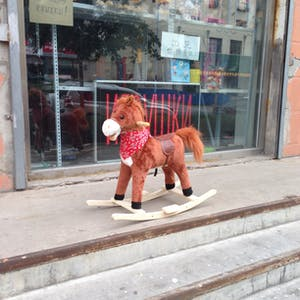 View enlargement of A brown rocking horse wears a red cowboy scarf.