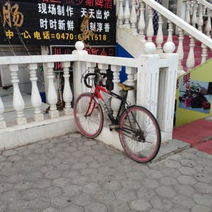 View enlargement of A 10 speed has narrow handlebars and pink rims.