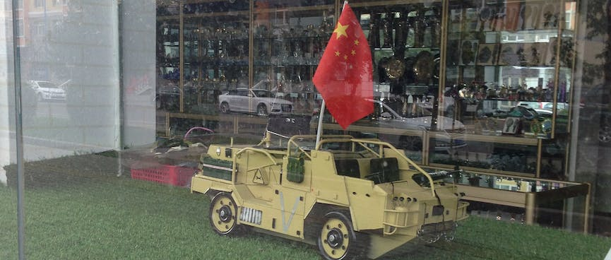 A scale model Armoured Personnel Vehicle is the size of a large cat and flies the Chinese flag.