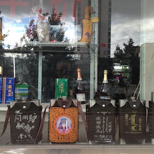 View enlargement of Hip flasks form a line in a shop window.