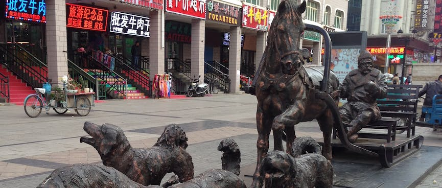 Bronze statues of four dogs and a horse, pulling the same man.