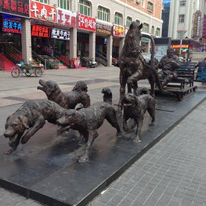 View enlargement of Bronze statues of four dogs and a horse, pulling the same man.