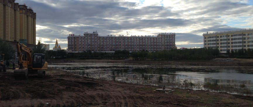 Large classical apartment blocks form a backdrop to muddy tyre tracks from two diggers.