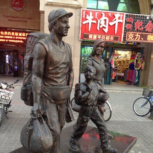View enlargement of Bronze statues of a fit man, wife and child.