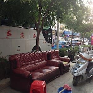 View enlargement of The footpath is filled with motorcycles and Shabby Chic leather couches.